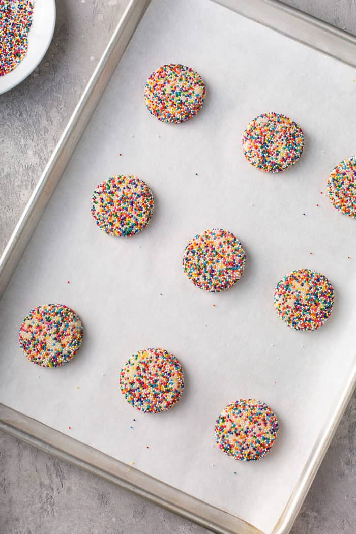 Flattened balls of funfetti cookie dough on a parchment-lined baking sheet