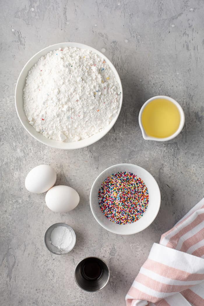 Ingredients for funfetti cookies on a gray countertop