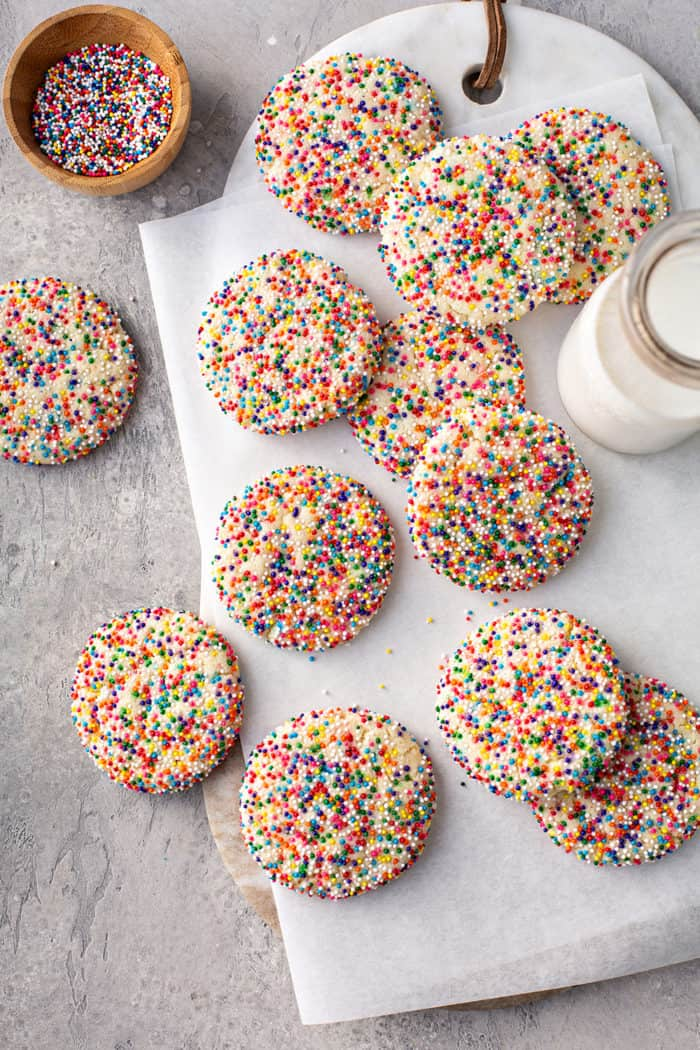 Funfetti cookies scattered across a piece of parchment paper, next to a glass of milk