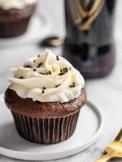 Guinness chocolate cupcake topped with vanilla buttercream and chocolate jimmies on a white plate in front of a Guinness bottle