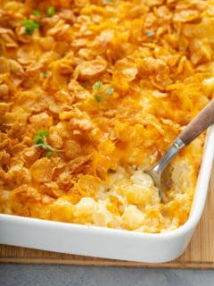 Spoon digging into the corner of a hash brown casserole in a white baking dish