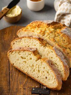 Sliced loaf of irish soda bread on a wooden cutting board
