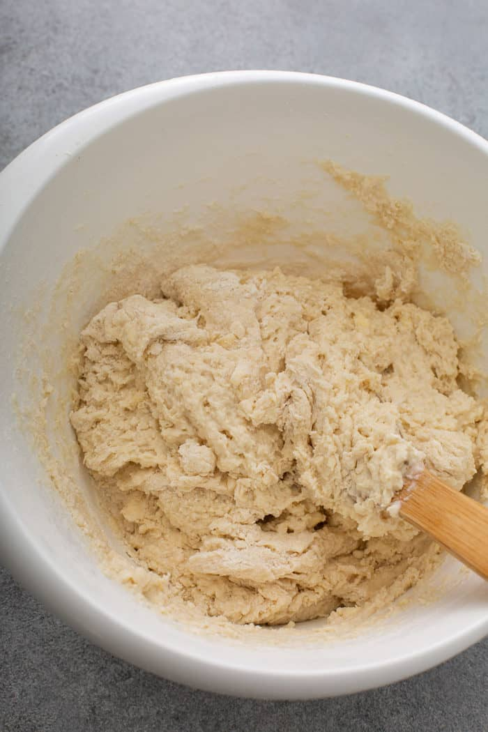Wooden spoon stirring Irish soda bread dough in a white mixing bowl