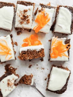 Slices of frosted carrot cake on a piece of parchment paper