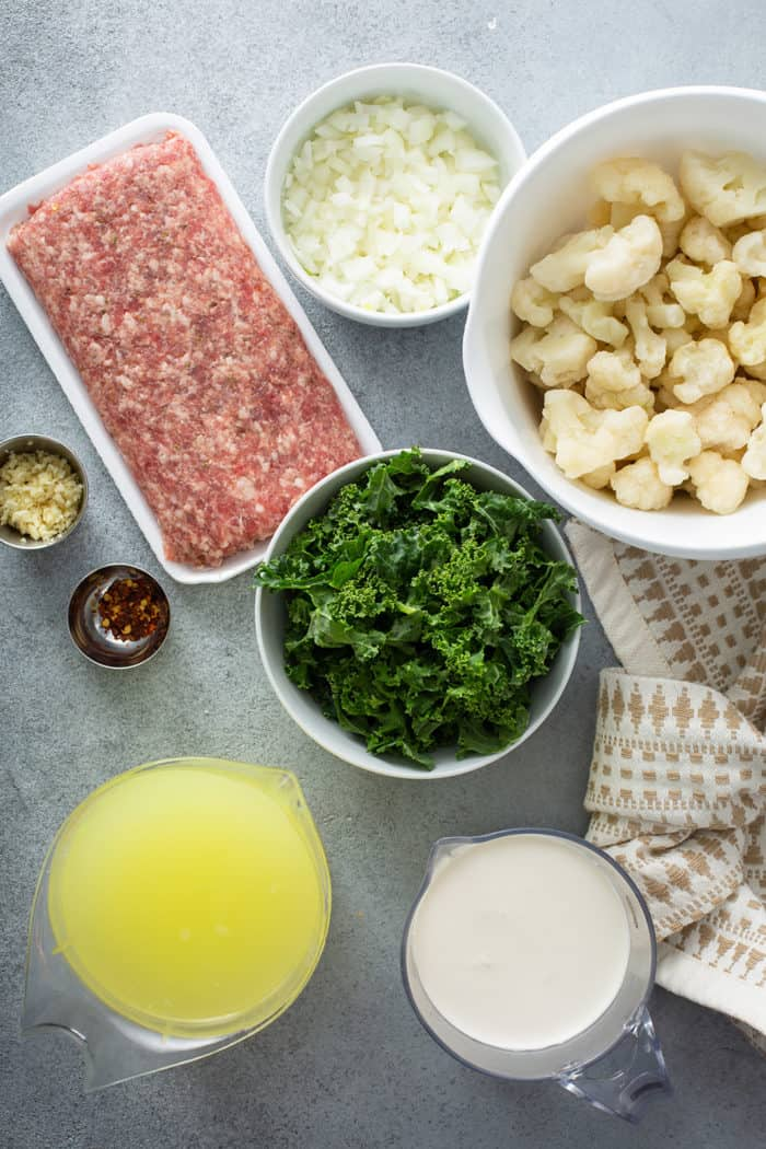 Ingredients for low carb zuppa toscana arranged on a gray countertop