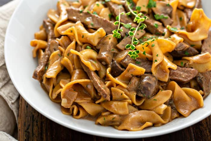 Close up of one-pot beef stroganoff in a white serving bowl, garnished with fresh thyme