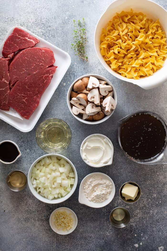 One-pot beef stroganoff ingredients arranged on a gray counter
