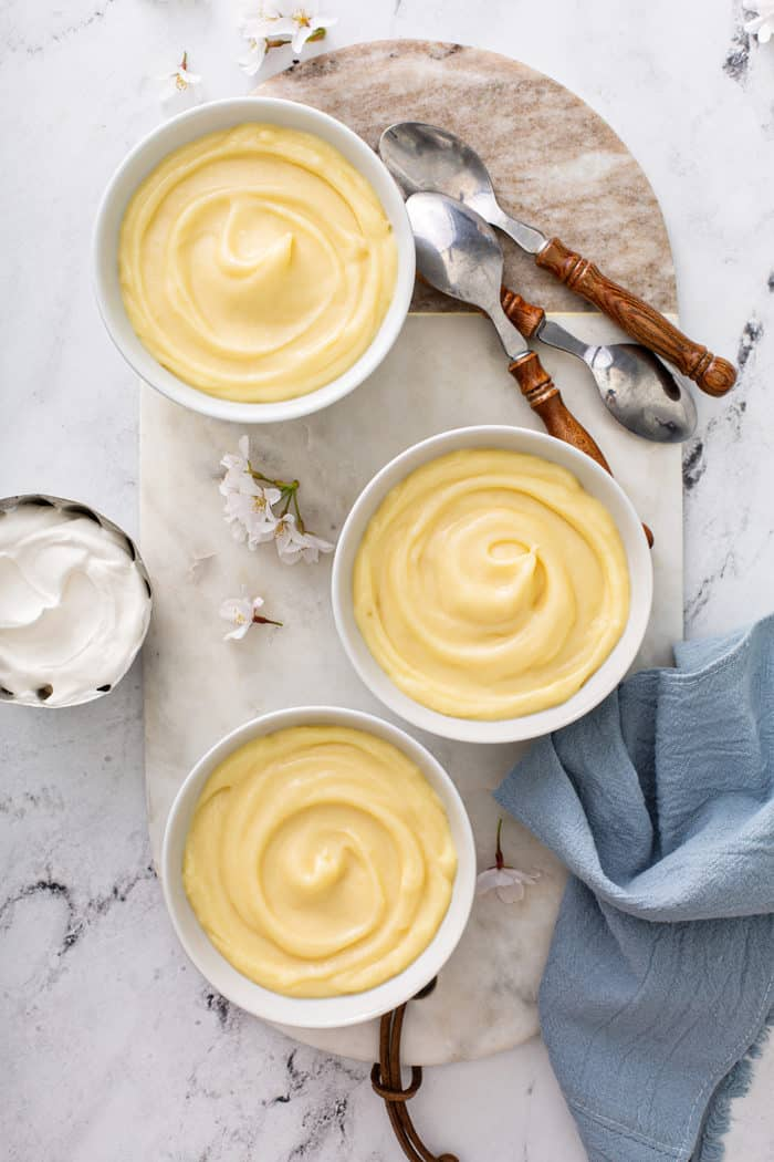 Overhead view of three white bowls of homemade vanilla pudding on a marble board, surrounded by spoons and homemade whipped cream