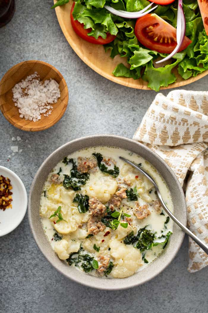 Overhead view of a bowl of zuppa toscana alongside a green salad and a cloth napkin