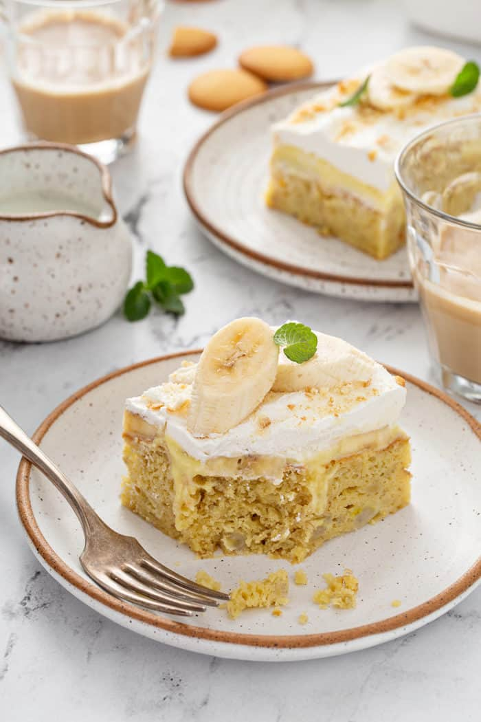 Slice of banana pudding poke cake with a bite taken out of it next to a fork on a white plate, with more plated slices of cake in the background