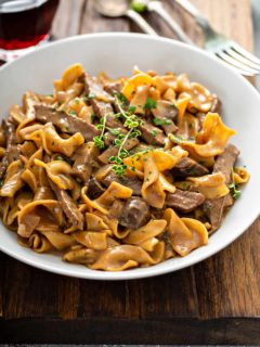 Bowl of one-pot beef stroganoff, topped with fresh thyme, on a wooden board