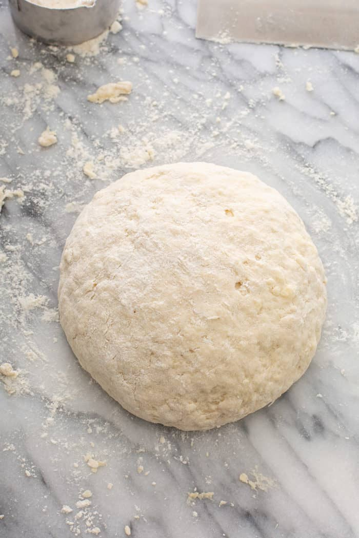 Shaped loaf of irish soda bread on a floured marble surface