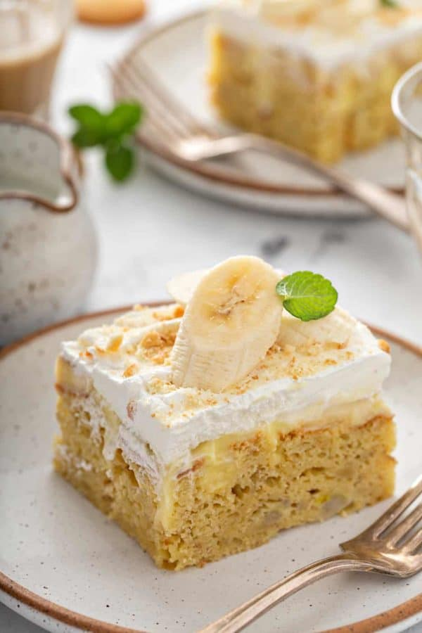 Slice of banana pudding poke cake garnished with a slice of banana on a white plate