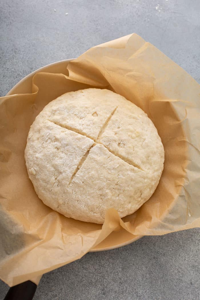 Loaf of soda bread dough in an iron skillet, ready to be baked