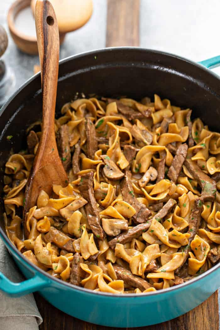Wooden spoon stirring one-pot beef stroganoff in a large dutch oven