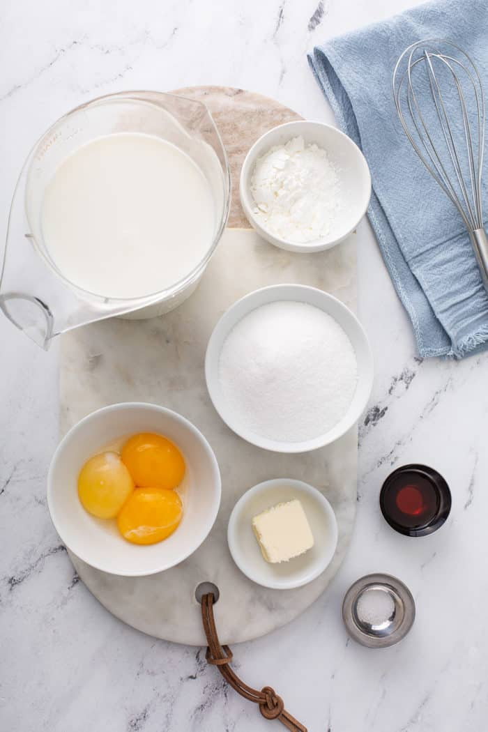 Homemade vanilla pudding ingredients on a marble countertop