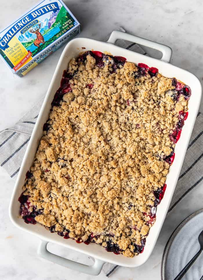Overhead view of baked berry crisp in a white baking dish, next to a carton of butter