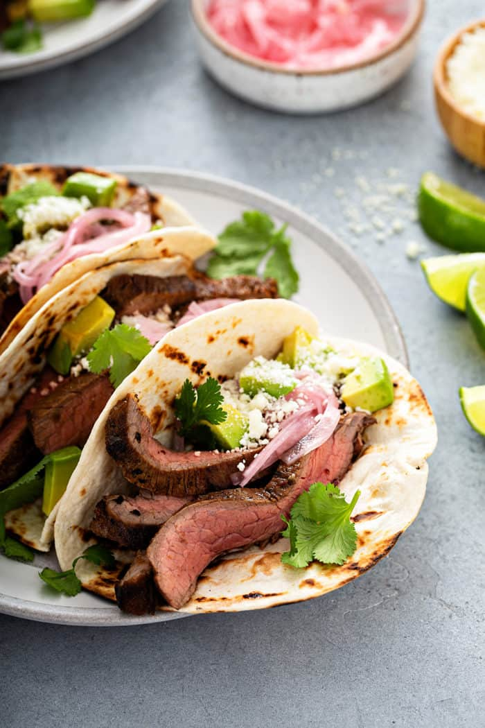Close up of a flank steak taco in a flour tortilla, topped with avocado, pickled onion and cilantro