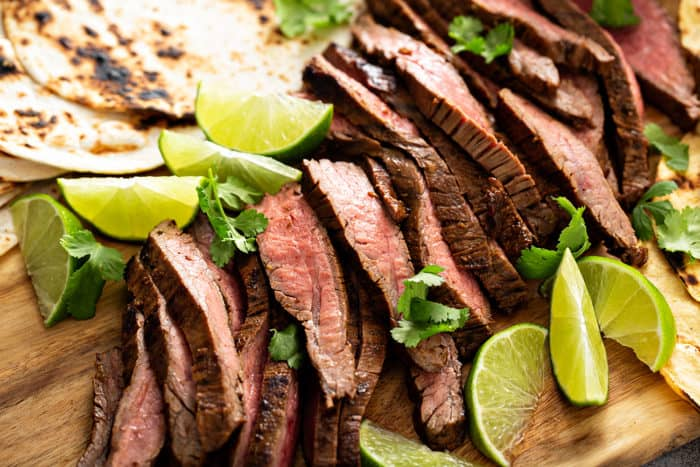 Close up of sliced flank steak surrounded by lime wedges on a wooden board