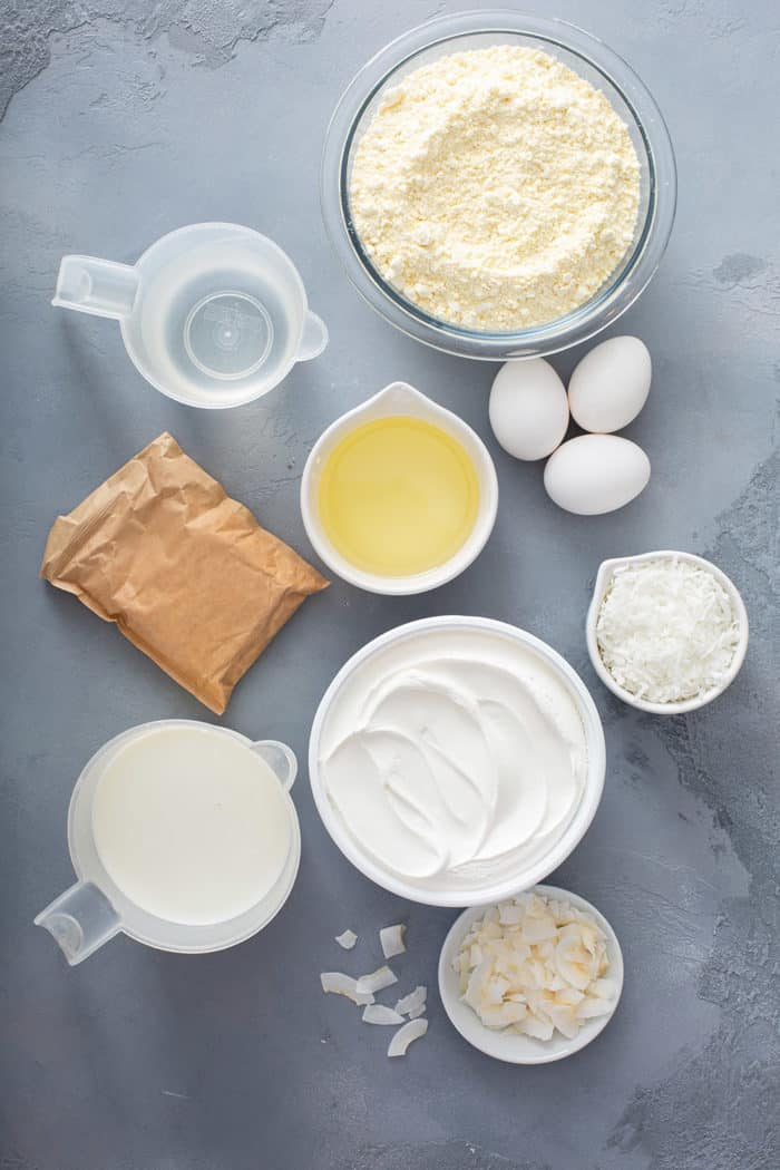Ingredients for coconut poke cake arranged on a gray countertop