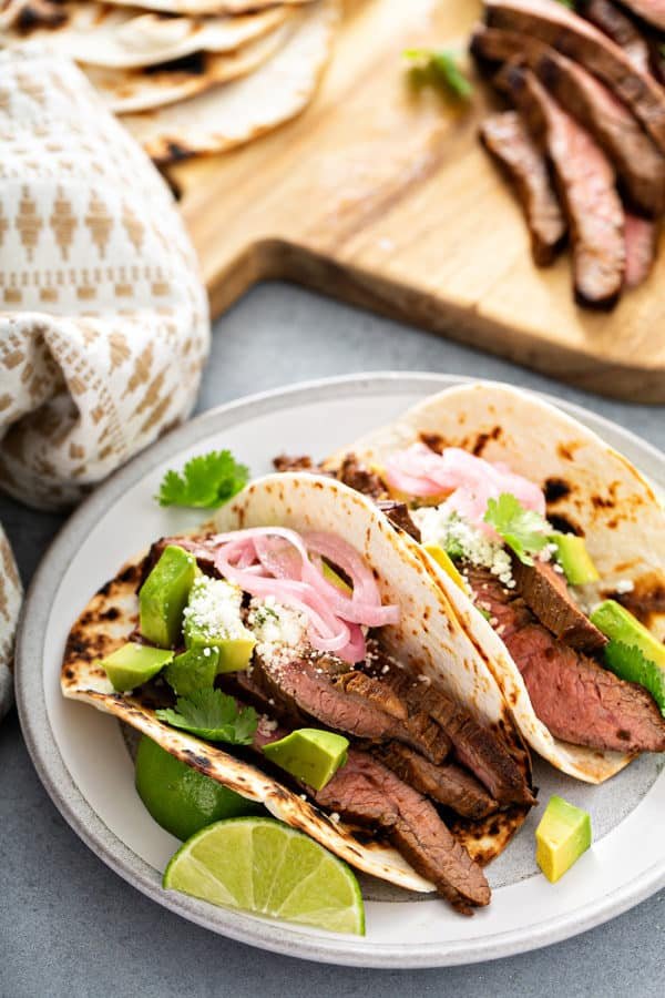Two flank steak tacos in charred flour tortillas on a white plate with a wooden cutting board in the background