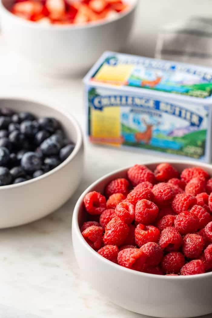 White bowls of fresh berries surrounding a carton of butter on a marble countertop