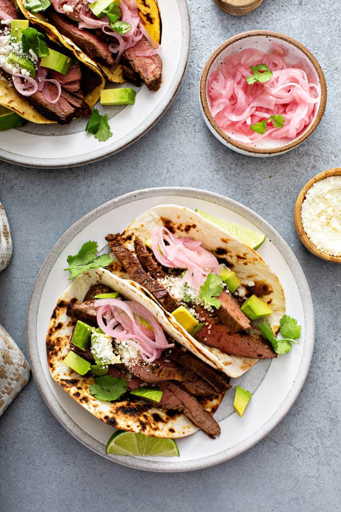 Overhead view of two white plates, each holding multiple flank steak tacos, next to bowls of pickled onions