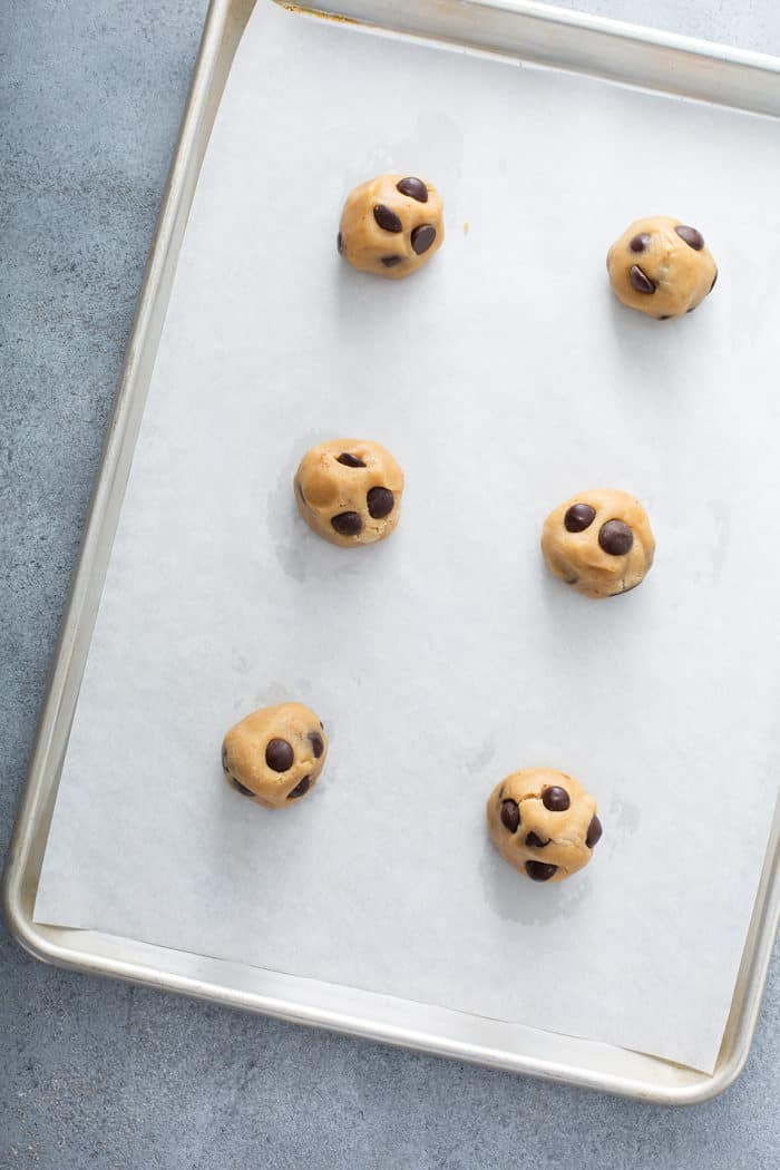 Six balls of brown butter cookie dough set on a parchment-lined baking sheet