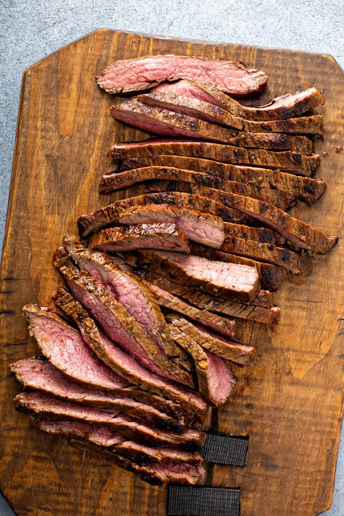 Sliced, grilled flank steak on a wooden cutting board
