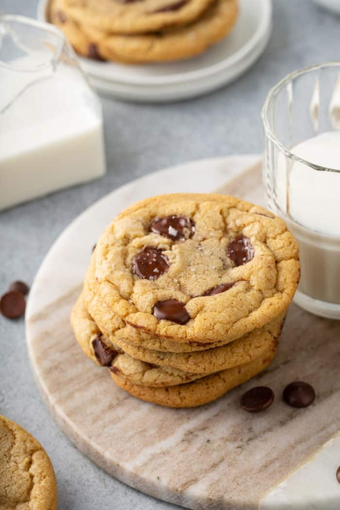 Five brown butter chocolate chip cookies stacked on a wooden board next to a glass of milk