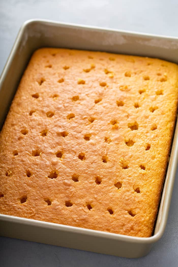 Baked yellow cake in a cake pan, with holes poked in it to turn it into a poke cake