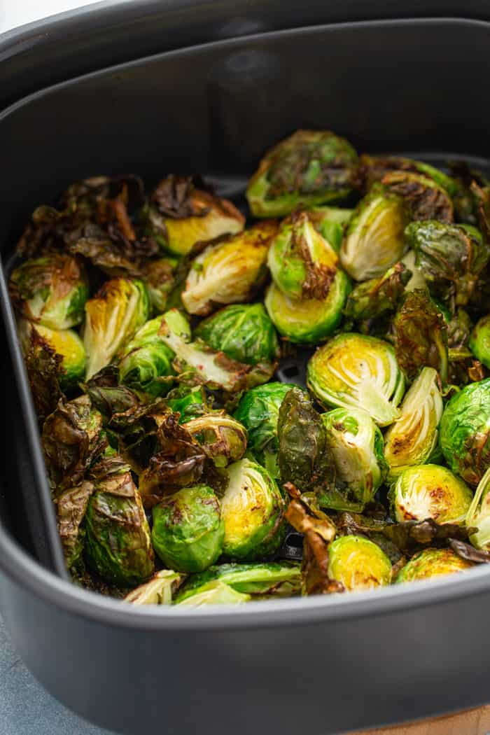 Crispy brussels sprouts fresh out of the air fryer, still in the fryer basket