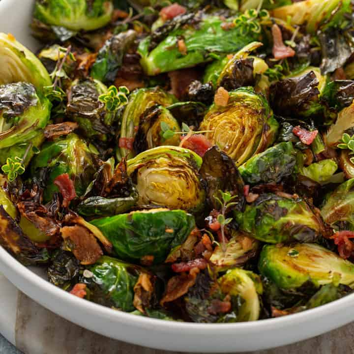 Air fried brussels sprouts tossed with bacon and balsamic in a white serving bowl