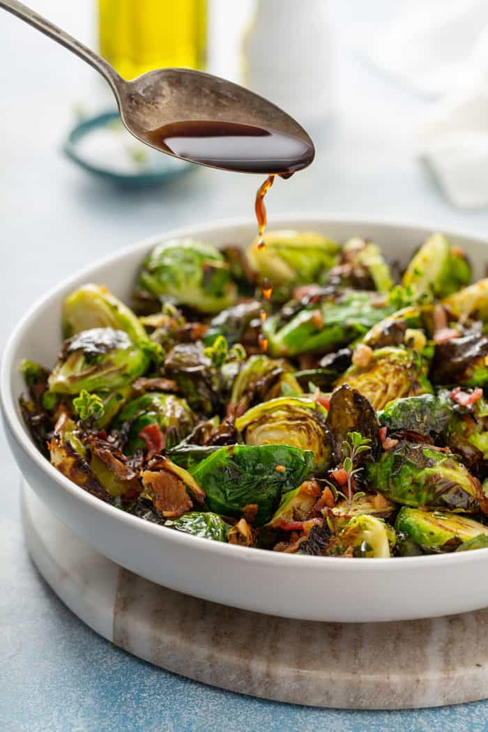 Spoon drizzling balsamic vinegar over air fried brussels sprouts in a white serving bowl