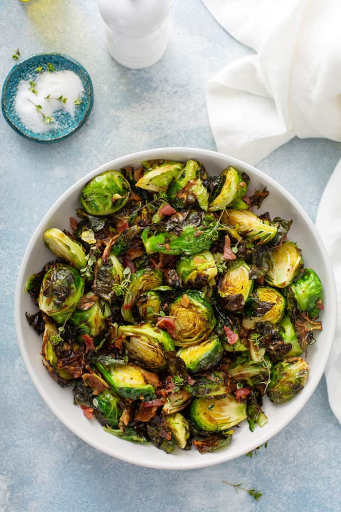 Overhead view of air fryer brussels sprouts in a white serving bowl on a blue counter