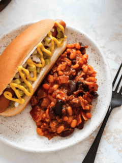 Old fashioned baked beans on a plate next to a hot dog