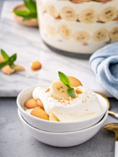 Magnolia bakery banana pudding in a small white serving dishes, with a trifle dish of the pudding in the background