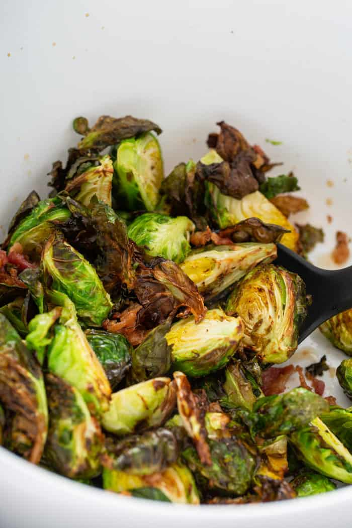 Freshly air fried brussels sprouts tossed with bacon in a white mixing bowl
