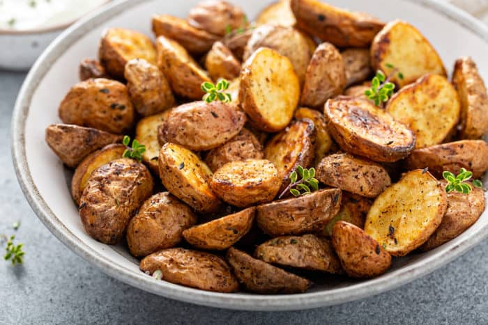 Roasted air fryer potatoes in a white serving bowl