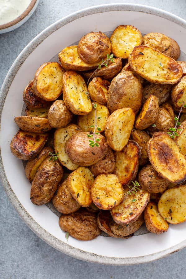 Overhead close up view of air fryer roasted potatoes in a white serving bowl