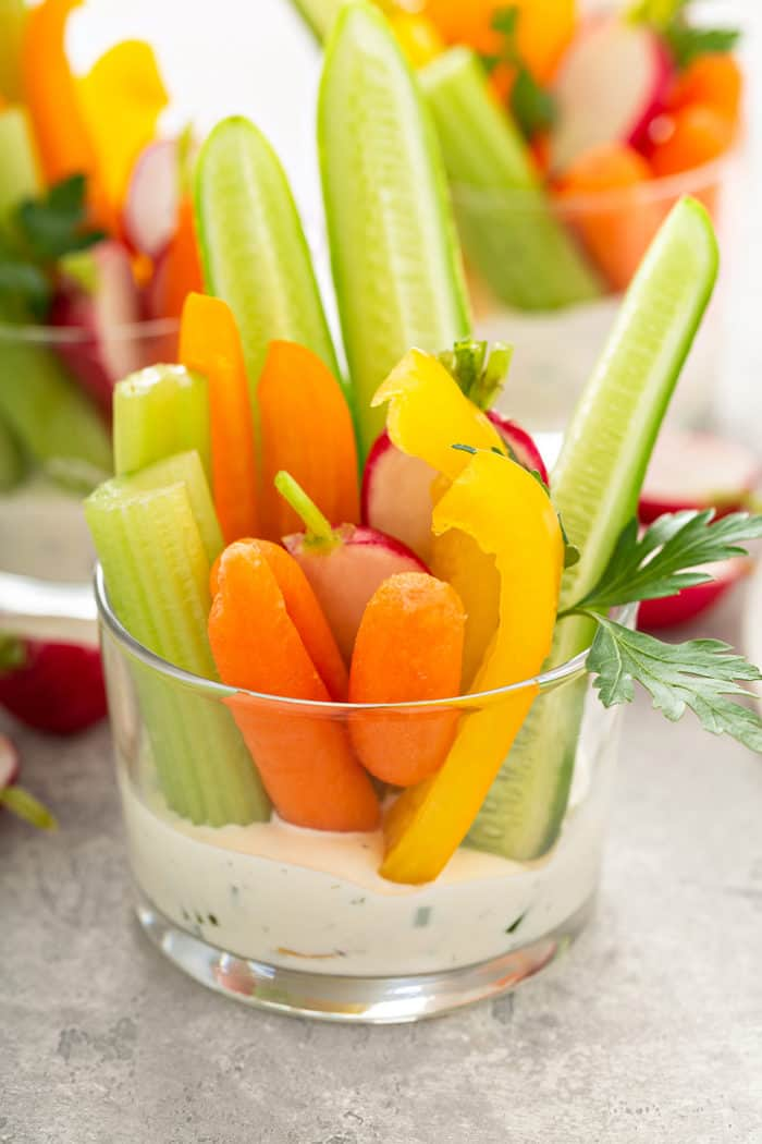 Glass cup with ranch dip on the bottom and cut veggies set into the dip