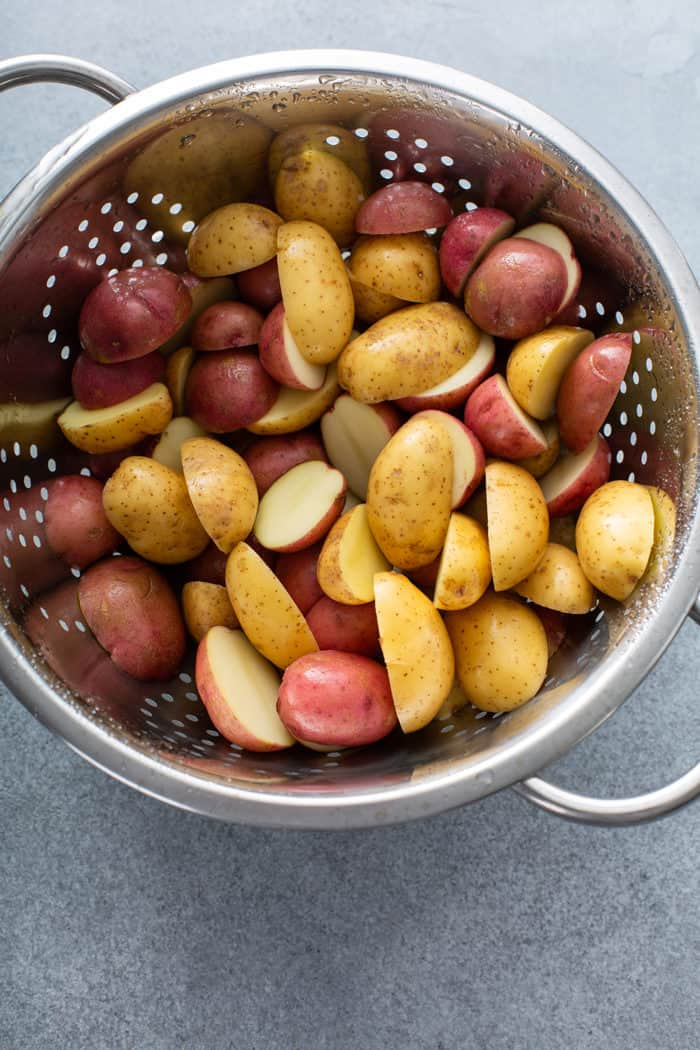 Sliced baby potatoes in a metal colander