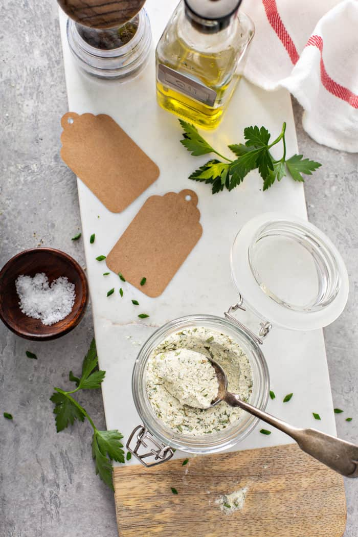 Overhead view of ranch seasoning in a glass jar, next to gift tags for gifting