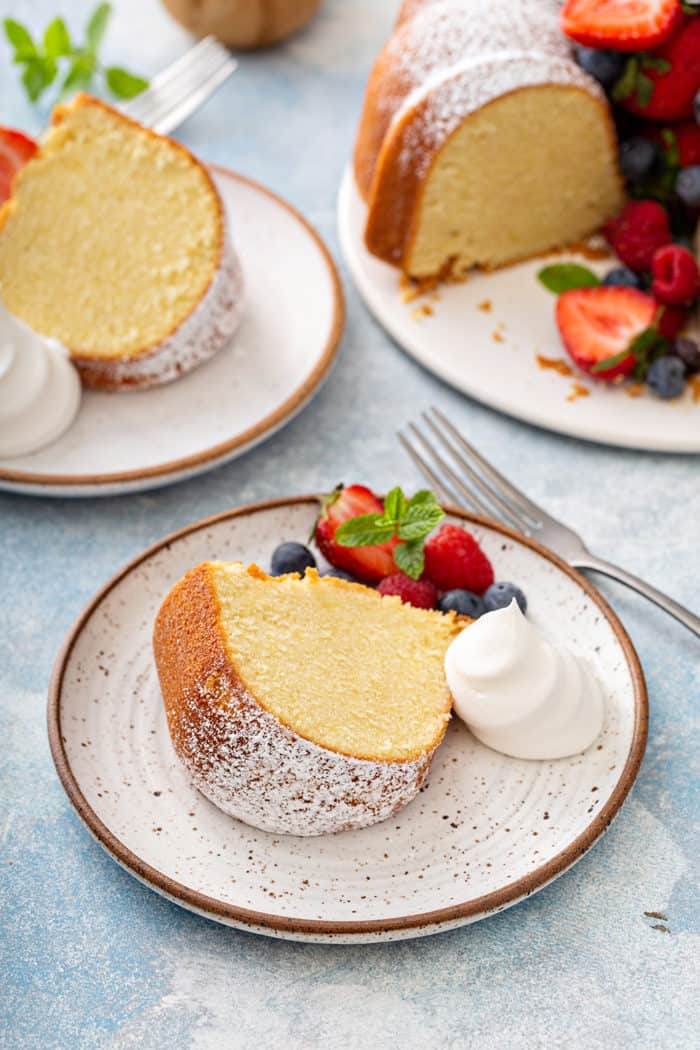 Plated slices of whipping cream cake, garnished with whipped cream and fresh berries