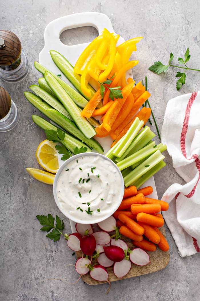 Overhead view of a bowl of ranch dip on a platter of crudites