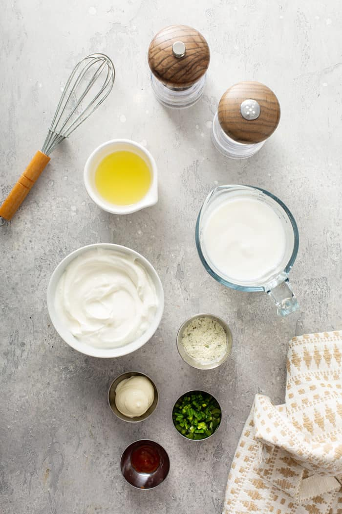 ingredients for homemade ranch dressing arranged on a gray countertop