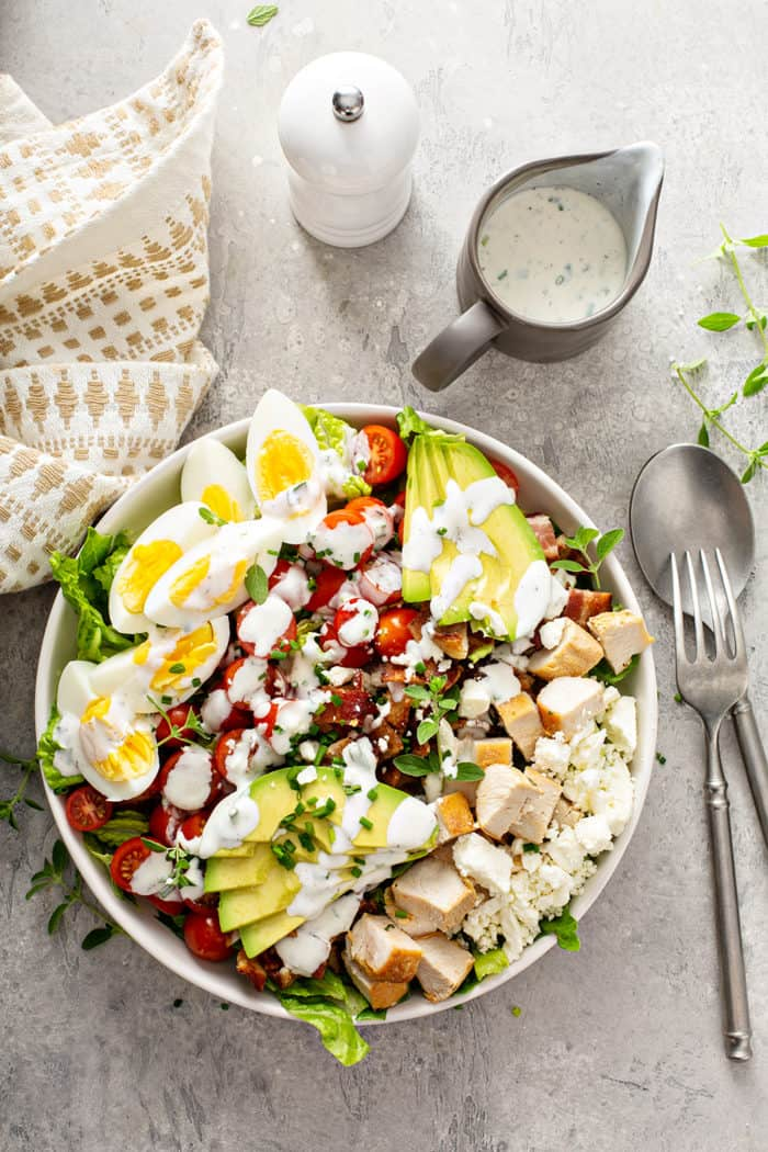Overhead view of a cobb salad topped with ranch dressing on a gray countertop
