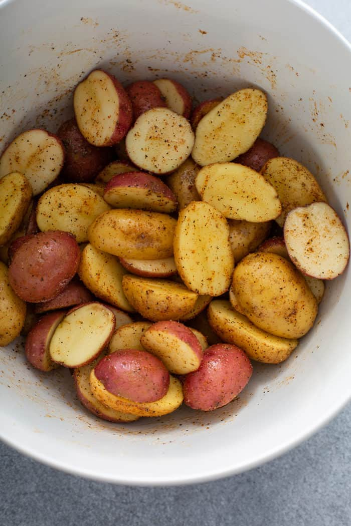 Bowl of seasoned halved potatoes, ready to go into the air fryer