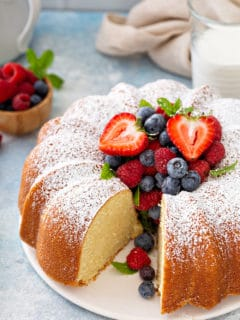 Sliced whipping cream cake on a white cake plate, garnished with fresh berries and powdered sugar