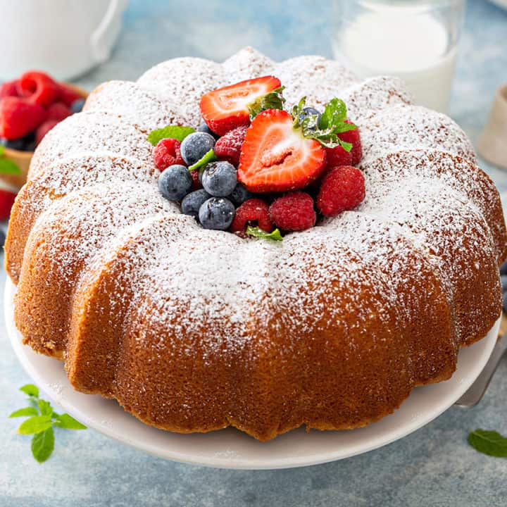 Baked whipping cream cake on a cake plate, with fresh berries piled in the center of the cake